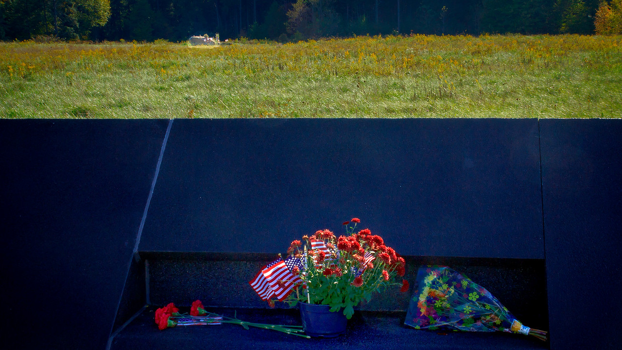 Memorial wall with crash site behind the wall. The Stone in the background marks the spot where the plane crashed and the wall markes the outer limits of the crash site. Only family members of the dead passengers are permitted inside the wall.