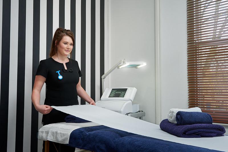 Beauty Therapist Preparing Massage Table