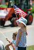 A girl waving an American flag watches the 2010 Peacham Independence Day Tractor Parade, Peacham, VT.