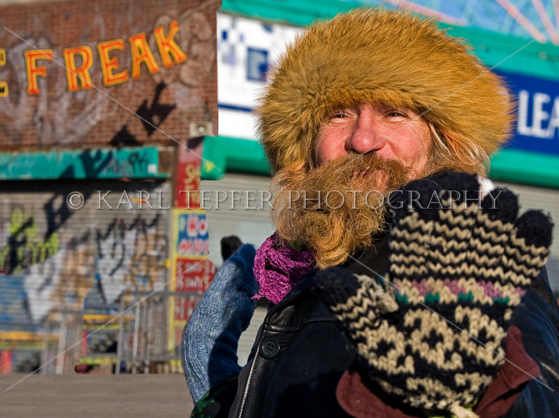 """<h2>This image was made on 1/1/09 on the world famous Coney Island Boardwalk during the annual Polar Bear Swim. It was about 20 degrees out and extremely windy.     <br>This fellow was standing in front of the famous """"SHOOT THE FREAK"""" boardwalk game and I captured this pose.  He was having a great time posing for me and was definitely not one of the polar bears who went swimming. Behind him are the now closed, probably forever, concessions and Astroland....you can see the ferris wheel on the upper right portion of the image.  <br> Coney Island may be torn down and never be the same, but human spirit endures.  Comments, as always, welcome...."""