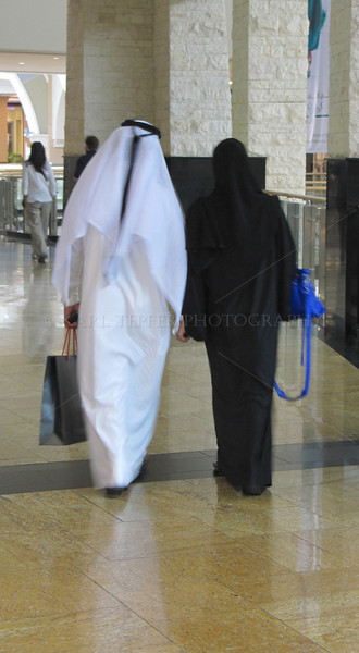 """These two were holding hands in the Mall of the Emirates (the largest mall in the world, which has an indoor ski village, """"Ski Dubai."""")<br /> I believe holding hands was one of the things not allowed according to that sign, but I gave this one a pass."""