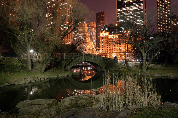 Gapstow Bridge at night in Central Park, Manhattan, New York City in the winter. Plaza Hotel in the background.