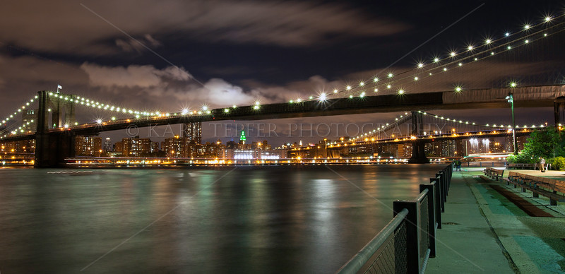 View from Brooklyn Bridge Park. Nearest bridge is the Brooklyn Bridge, further back is the Manhattan Bridge. The Empire State Building is off in the distance, lit with green lights for a movie opening that evening.