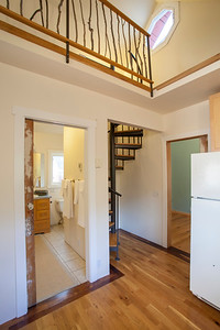 The bathroom and office open off the kitchen and a spiral staircase climbs to the loft above.