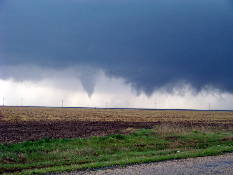 The funnel on the left is what's left of the old wall cloud, and begins to spin rapidly. On the right of that is the new wall cloud and funnel poking down.