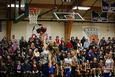 Fans fill the bleachers as Eagle Morgan Duak goes for a lay up  against Mariner Katie Hutchinson. Photo by Anne Berleant