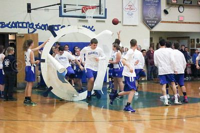 The Mariner boys enter the court December 9, with an assist from the Lady Mariners. Photo by Anne Berleant