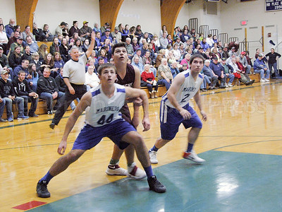 From left, Mariner Mason Oliver, left, Eagle Stefan Simmons, and Mariner Silas Bates wait for the rebound. Photo by Jack Scott