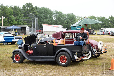 The right idea.  On a rainy Saturday morning, Ken Way of Richmond sits under an umbrella fixed to his vintage 1928 Model A Ford Roadster pickup.  Ken Way who has been a mechanic all his life restored this truck in less than a year.  The truck has a 1953 flathead V8 engine.  Photo by Franklin Brown