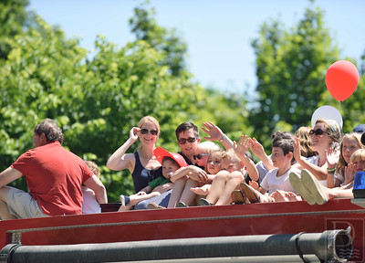 All aboard!  Several children wave to passersby as the Castine Fire Department offered free firetruck rides around the block during July 4th.  Photo by Franklin Brown