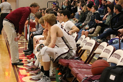 Coach Dwayne Carter confers with his starters. Photo by Anne Berleant