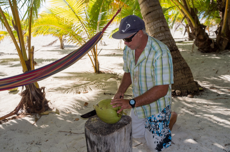Guide cutting up a coconut for us to taste the fresh water & meat