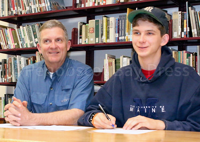 John Hassett signs a letter of intent to attend University of Maine on a track and cross country athletic scholarship. Photo by Monique Labbe