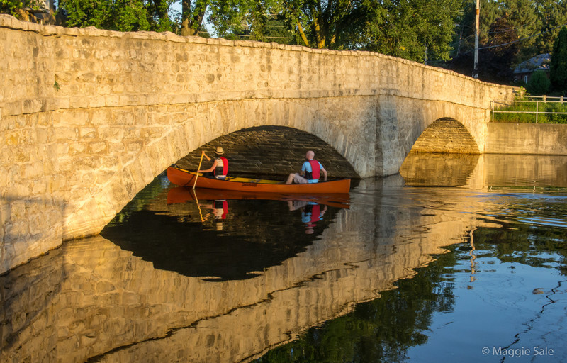Canoeists on the Speed River going under Gow Bridge in Guelph on a lovely summer's evening.