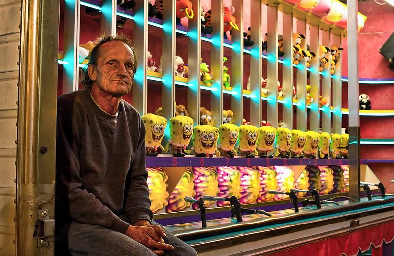 Sad carnival man with happy spongebobs