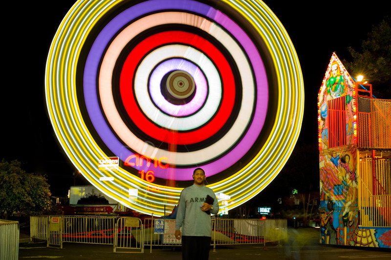 This is the ride with two spaceships that spin in a circle. WIth random bystander. 4 second exposure.