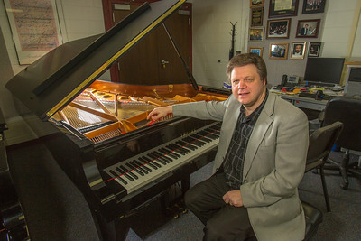 UAF Professor Eduard Zilberkant sits at the Yamaha disklavier temporarily stored in his office. The instrument is being used in the summer of 2014 for the international piano e-competition hosted on the Fairbanks campus.  Filename: AAR-14-4179-35.jpg