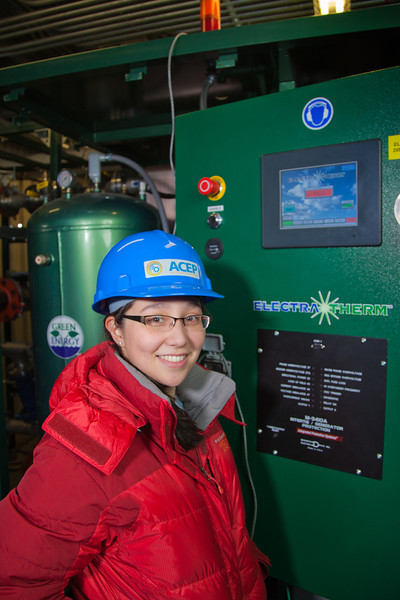 """Graduate student Lisa Stowell inspects newly installed equipment in the UAF power plant designed to help capture heat generated by diesel engines.  <div class=""""ss-paypal-button"""">Filename: AAR-11-3245-191.jpg</div><div class=""""ss-paypal-button-end"""" style=""""""""></div>"""