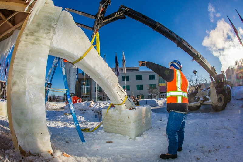 "Volunteers from GHEMM, Inc. use a crane to lift the buttresses for this year's student-built ice arch into position in Cornerstone Plaza on campus. The annual ice arch is designed and built by a team of engineering students, a UAF tradition going back more than 60 years.  <div class=""ss-paypal-button"">Filename: AAR-14-4078-46.jpg</div><div class=""ss-paypal-button-end""></div>"