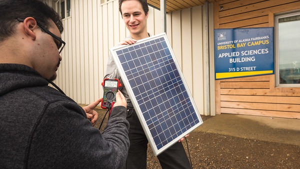 Assistant Professor Tom Marsik, right, demonstrates how a solar panel can generate electricity from daylight with undergraduate Andrew Akelkok at UAF's Bristol Bay Campus in Dillingham.  Filename: AAR-16-4860-248.jpg