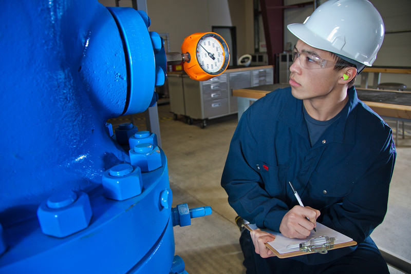 """Stefan Weingarth checks the reading on the oil well head at CTC's process technology facility on Van Horn Road.  <div class=""""ss-paypal-button"""">Filename: AAR-11-3230-014.jpg</div><div class=""""ss-paypal-button-end"""" style=""""""""></div>"""