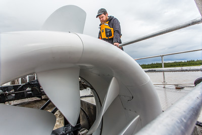 Jeremy Kasper, a research assistant professor with UAF's Alaska Center for Energy and Power (ACEP), inspects a turbine mounted on a barge anchored in the Tanana River near Nenana. The device is being tested to determine its feasibility as a means of producing electricity generated from the current of the river.  Filename: AAR-15-4577-029.jpg