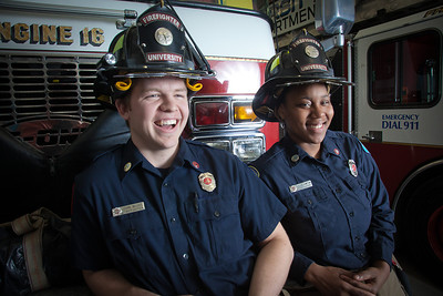 UAF student firefighters/EMTs John McGee and Lillian Hampton pose in front of one of the firetrucks housed in the Whitaker Building on the Fairbanks campus.  Filename: AAR-11-3223-138.jpg