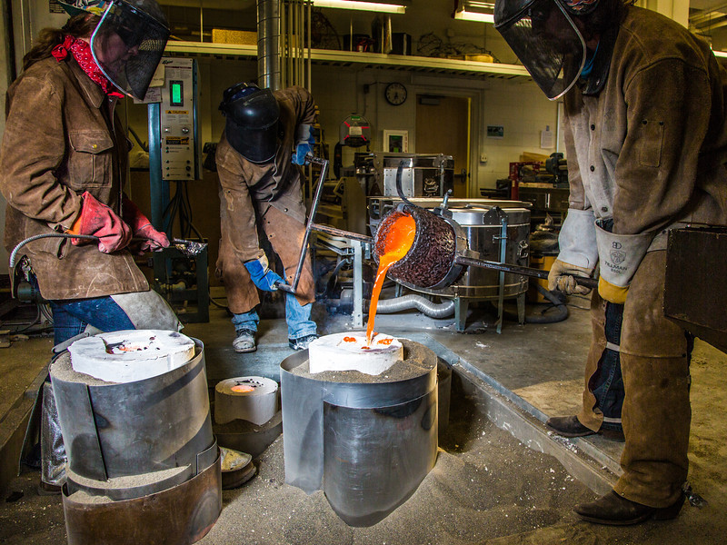 "Art major Joel Isaak, center, get some help filling a mold with molten bronze as part of the process of creating a life-sized sculpture for his senior thesis in the UAF Fine Arts complex.  <div class=""ss-paypal-button"">Filename: AAR-12-3347-097.jpg</div><div class=""ss-paypal-button-end"" style=""""></div>"