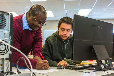 UAF Chukchi Campus Assistant Professor of Developmental Math Kelechukwu Alu works one-on-one with a student during a morning class at the Alaska Technical Center in Kotzebue.  Filename: AAR-16-4863-323.jpg