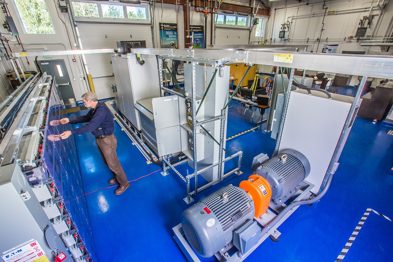 """Research technician David Light works with the battery bank in one of the modules in the Alaska Center for Energy and Power Technology Center.  <div class=""""ss-paypal-button"""">Filename: AAR-12-3479-039.jpg</div><div class=""""ss-paypal-button-end"""" style=""""""""></div>"""