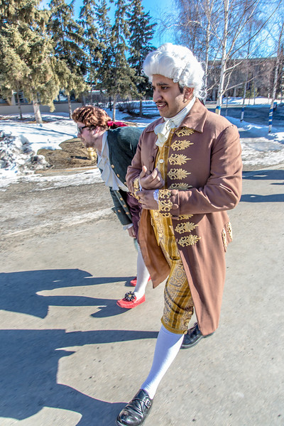 """Brian Tuohy, playing the title role in Theatre UAF's production of """"Tartuffe,"""" (left) and Sambit Misra, playing Orgon, walk across campus before performing a live teaser in Wood Center a couple of days before opening night.  <div class=""""ss-paypal-button"""">Filename: AAR-14-4121-26.jpg</div><div class=""""ss-paypal-button-end"""" style=""""""""></div>"""