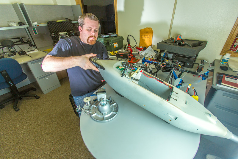 "Technician Michael Cook works on one of the unmanned aerial vehicles in UAF's Alaska Center for Unmanned Aircraft Systems Integration (ACUASI) shop in south Fairbanks.  <div class=""ss-paypal-button"">Filename: AAR-13-4026-71.jpg</div><div class=""ss-paypal-button-end""></div>"