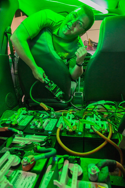 """Engineering major Karlin Swearingen hooks up batteries in a modified Subaru as part of a project in electric car conversion techniques. (Note: Taken as part of commercial shoot with Nerland Agency. Pretend class -- use with discretion!)  <div class=""""ss-paypal-button"""">Filename: AAR-12-3561-06.jpg</div><div class=""""ss-paypal-button-end"""" style=""""""""></div>"""