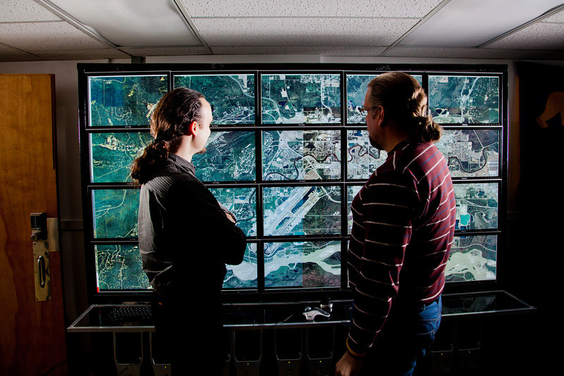 """Computer science faculty members Orion Lawlor, left, and Jon Genetti inspect a high resolution aerial photo of Fairbanks on the bioinformatics powerwall in the Chapman Building.  <div class=""""ss-paypal-button"""">Filename: AAR-12-3272-125.jpg</div><div class=""""ss-paypal-button-end"""" style=""""""""></div>"""