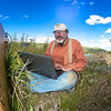 "Jack Schmid, a research professionals with the Alaska Center for Energy and Power, enters data at a remote recording station set up on the banks of the Tanana River near Nenana. Schmid is part of a team conducting research on the feasibility of using the river current to generate electricity for potential use throughout rural Alaska.  <div class=""ss-paypal-button"">Filename: AAR-12-3500-187.jpg</div><div class=""ss-paypal-button-end"" style=""""></div>"