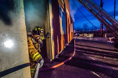 Student firefighter Ethan Stevenson exits a burning building during a live training drill at the Fairbanks Fire Training Center in South Fairbanks. McClean was one of about 30 students participating in the University Fire Department's Tuesday night drill Oct. 22.  Filename: AAR-13-3978-135.jpg
