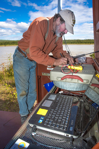 """Jack Schmid, a research professionals with the Alaska Center for Energy and Power, enters data into a remote recording station set up on the banks of the Tanana River near Nenana. Schmid is part of a team conducting research on the feasibility of using the river current to generate electricity for potential use throughout rural Alaska.  <div class=""""ss-paypal-button"""">Filename: AAR-12-3500-163.jpg</div><div class=""""ss-paypal-button-end"""" style=""""""""></div>"""