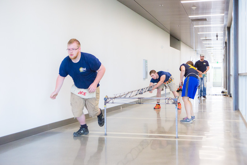 """Nathan Barnett dashes to retrieve a part for the bridge during the 2016 UAF Steel Bridge team's practice in the hallway of the Duckering Building before competing in the national competition.  <div class=""""ss-paypal-button"""">Filename: AAR-16-4888-11.jpg</div><div class=""""ss-paypal-button-end""""></div>"""