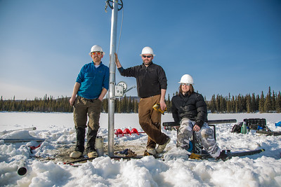 Associate Professor Mat Wooller, blue shirt, and Ph.D. candidate Jim Shobe, center, test a new vibra-coring system through a hole in lake ice to sample long cores of sediment deep below the lake's bottom. Also helping is Terry Smith, right, a North Pole High School student intern.  Filename: AAR-12-3346-127.jpg