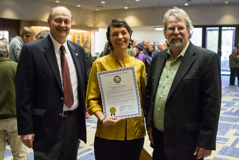 """Members of the Alaska legislature Rep. Dave Guttenberg and Sen. Joe Thomas present UAF Film department head Maya Salganek with a copy of the proclamation. The state voted to continue to offer economic incentives for film and television producers to shoot in Alaska. Salganek was vital in organizing a grassroots campaign that demonstrated strong support for the program.  <div class=""""ss-paypal-button"""">Filename: AAR-12-3558-49.jpg</div><div class=""""ss-paypal-button-end"""" style=""""""""></div>"""