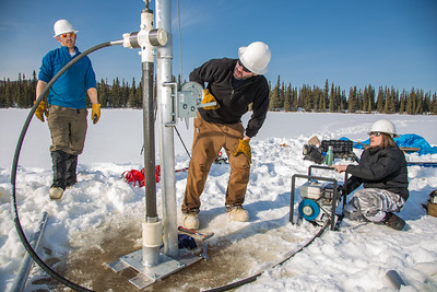 Associate Professor Mat Wooller, blue shirt, and Ph.D. candidate Jim Shobe, center, test a new vibra-coring system through a hole in lake ice to sample long cores of sediment deep below the lake's bottom. Also helping is Terry Smith, right, a North Pole High School student intern.  Filename: AAR-12-3346-050.jpg