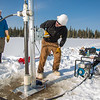 "Associate Professor Mat Wooller, blue shirt, and Ph.D. candidate Jim Shobe, center, test a new vibra-coring system through a hole in lake ice to sample long cores of sediment deep below the lake's bottom. Also helping is Terry Smith, right, a North Pole High School student intern.  <div class=""ss-paypal-button"">Filename: AAR-12-3346-050.jpg</div><div class=""ss-paypal-button-end"" style=""""></div>"