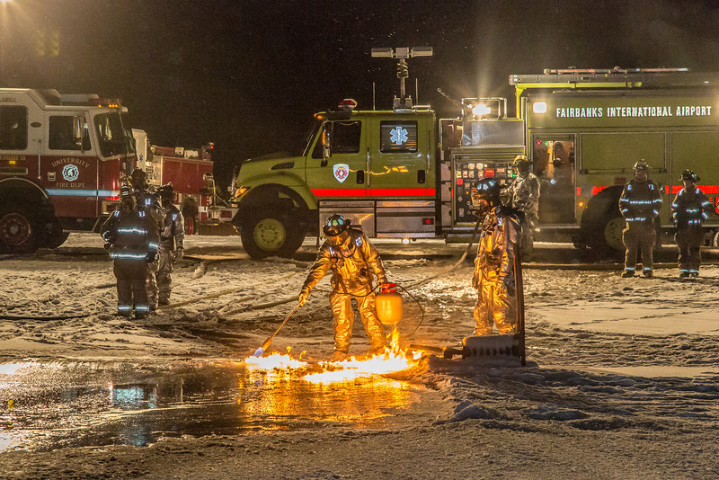 """Firefighters with the Fairbanks International Airport light a blaze to simulate a jet fuel fire during a live drill with students of the University Fire Department.  <div class=""""ss-paypal-button"""">Filename: AAR-13-3995-90.jpg</div><div class=""""ss-paypal-button-end"""" style=""""""""></div>"""