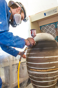 Art major Ian Wilkinson applies glaze from an airbrush under a temporary visqueen tent set up in the ceramics studio. The large pot is part of his BFA thesis project which opens next week in the UAF Fine Arts gallery.  Filename: AAR-13-3768-31.jpg