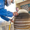 """Art major Ian Wilkinson applies glaze from an airbrush under a temporary visqueen tent set up in the ceramics studio. The large pot is part of his BFA thesis project which opens next week in the UAF Fine Arts gallery.  <div class=""""ss-paypal-button"""">Filename: AAR-13-3768-31.jpg</div><div class=""""ss-paypal-button-end"""" style=""""""""></div>"""