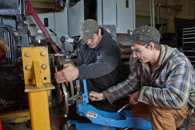 """Tony Craig, left, and George Jensen work together disassembling a transmission in the diesel mechanics lab at the Hutchison Institute of Technology.  <div class=""""ss-paypal-button"""">Filename: AAR-12-3312-092.jpg</div><div class=""""ss-paypal-button-end"""" style=""""""""></div>"""