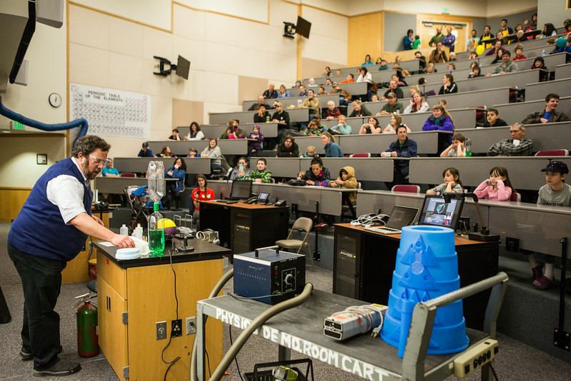 """Children and their parents receive a physics lecture from David Newman during Science Potpourriat the Reichardt Building.  <div class=""""ss-paypal-button"""">Filename: AAR-14-4141-87.jpg</div><div class=""""ss-paypal-button-end""""></div>"""