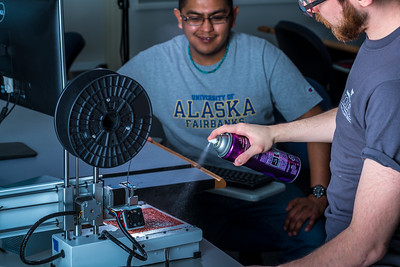 Program lab assistant Joel Sturm applies hair spray before junior science major Arch Chauhan starts printing during an open work session in UAF's Community and Technical College's 3-D print lab in downtown Fairbanks.  Filename: AAR-16-4857-046.jpg