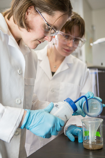 """Assistant professor Sarah Hayes, left, works with senior Kjersten Williams to complete a procedure in a Reichardt Building chemstry lab.  <div class=""""ss-paypal-button"""">Filename: AAR-12-3598-013.jpg</div><div class=""""ss-paypal-button-end"""" style=""""""""></div>"""