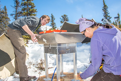Daisy Huang, a research engineer for the Alaska Center for Energy and Power, works with intern Luke George to level a SODAR station on a hillside near the Black Rapids Lodge. The station uses sound waves to measure atmospheric distrubances to produce a profile of wind speed and direction at a range of altitudes.  Filename: AAR-13-3843-12.jpg